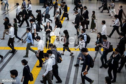 Japanese woman talking on the mobile phone surrounded by commuters walking to work.