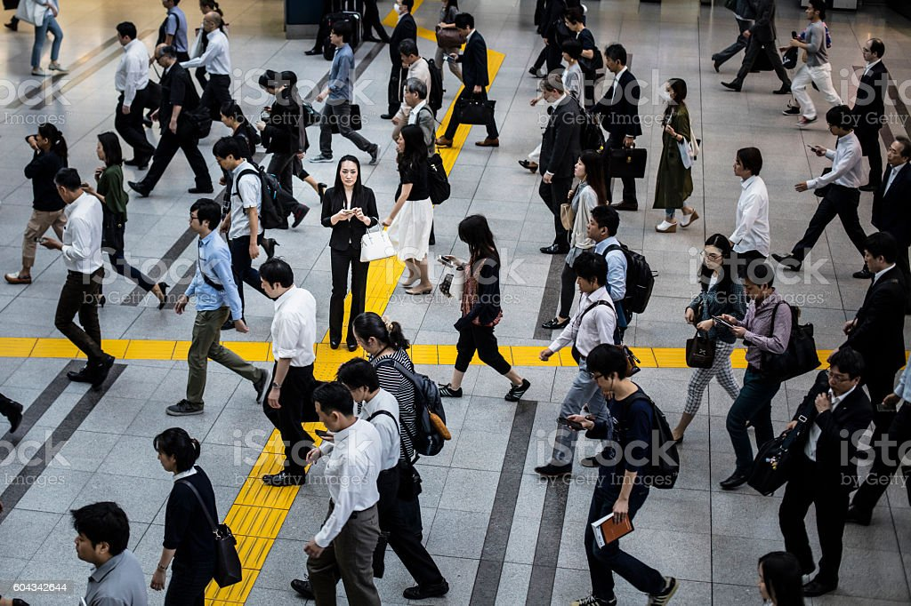 Japanese woman talking on the mobile phone surrounded by commuters stock photo