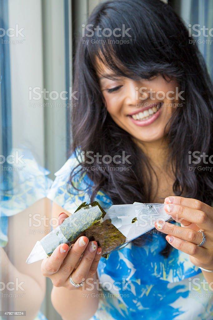 Japanese woman unwraping Onigiri stock photo