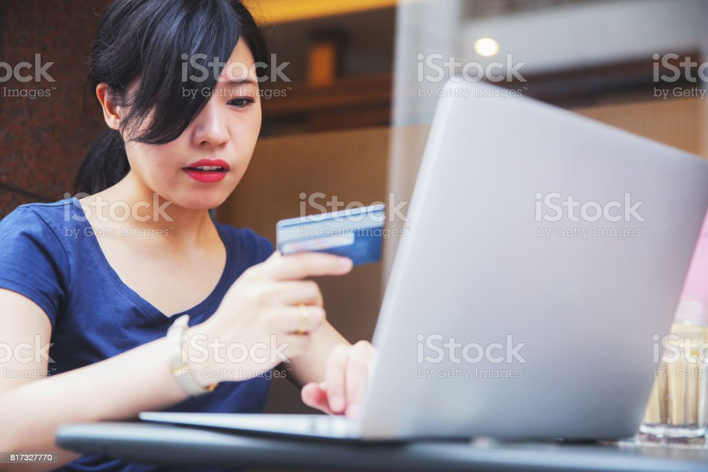 Japanese woman using her credit card to do online shopping stock photo