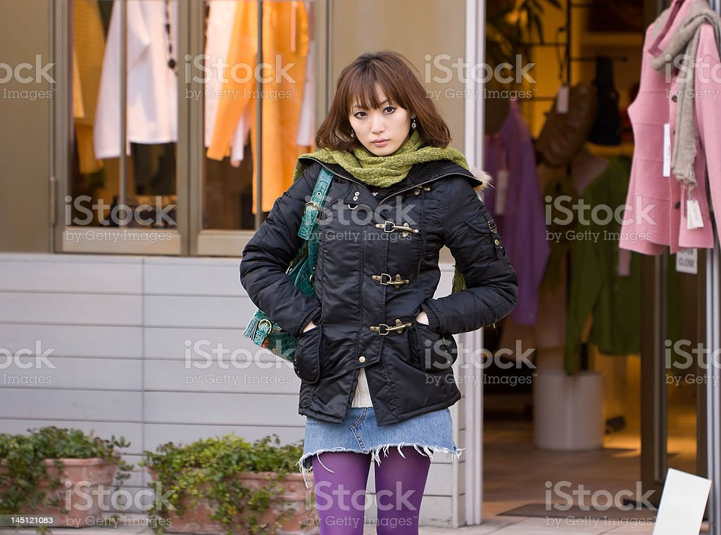 Japanese woman waits A young Japanese woman waits in front of a clothing store in a fashionable district of Tokyo, Japan. 20-24 Years Stock Photo