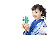 Japanese woman wearing yukata holding a mosquito coil of incense