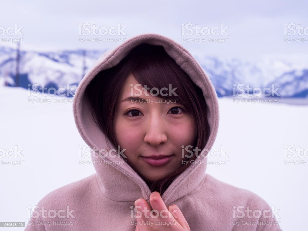 A Japanese woman who is having a hooded coat in the snow. stock photo