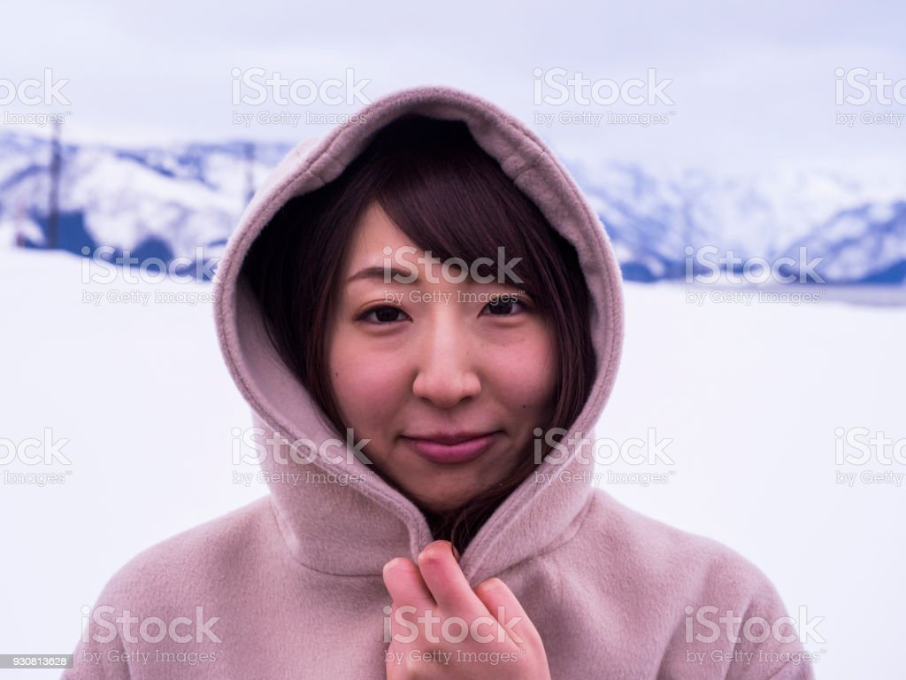 A Japanese woman who is having a hooded coat in the snow stock photo