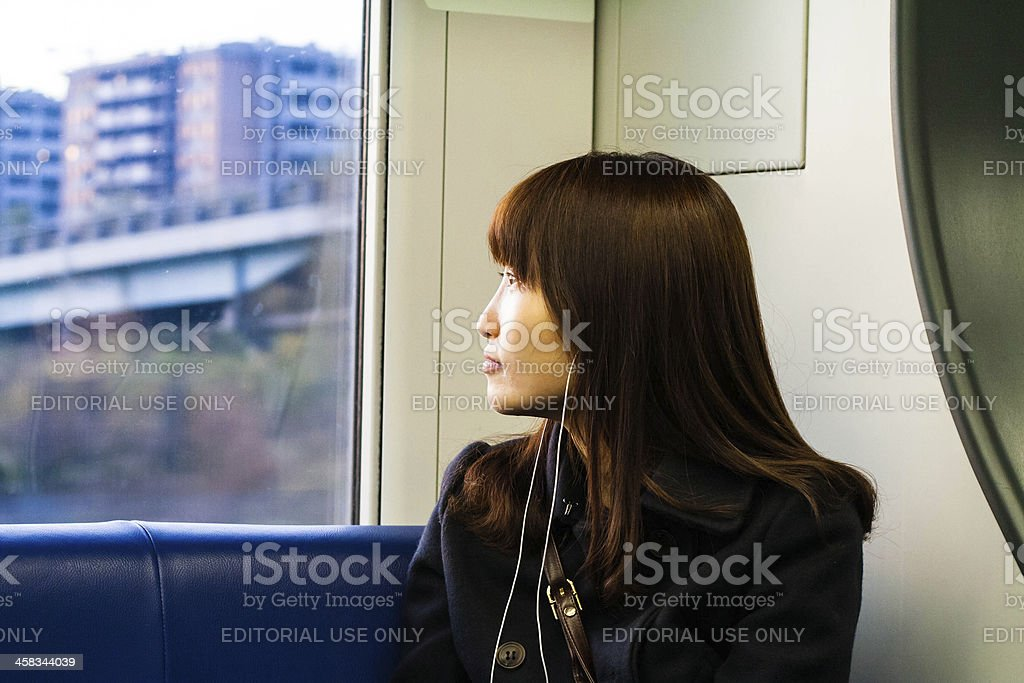 Japanese Woman with MP3 Player in Train royalty-free stock photo