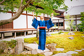 This is a horizontal, full frame color photograph of a mature Japanese woman dressed in a traditional blue kimono while visiting a temple in Kyoto, Japan. She opens her arms and looks up radiantly toward the sky. Photographed with a Nikon D800 DSLR camera.