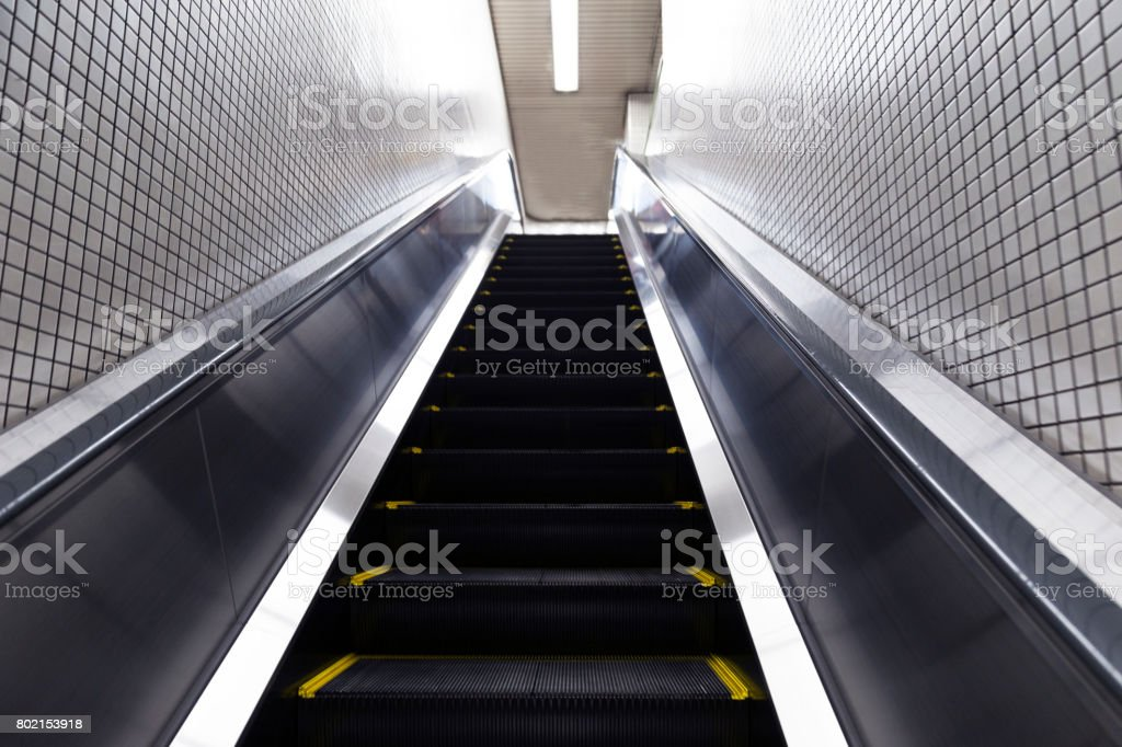 Japanese woman with shopping bags going up the escalator stock photo