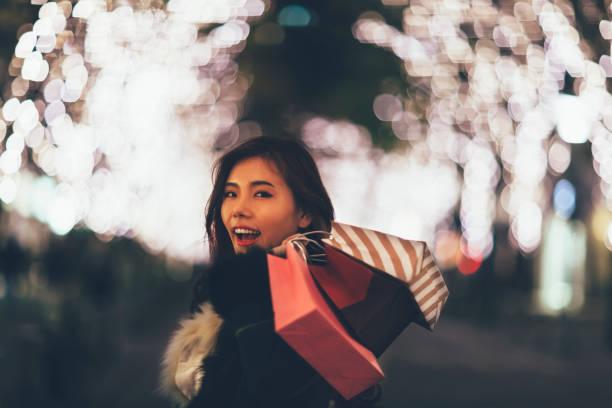 japanische frau mit einkaufstüten - weihnachten japan stock-fotos und bilder