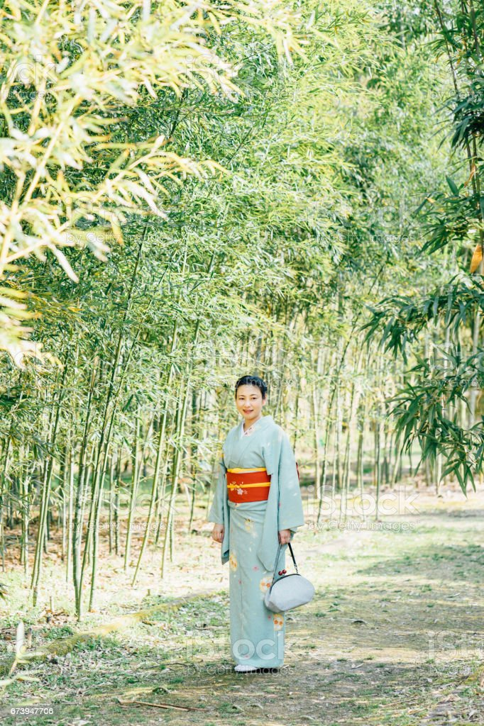 Japanese woman with typical yukata clothes in bamboo forest royalty-free stock photo