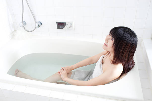 japanese woman wrapped in towel in the bathtub - japanese bath woman bildbanksfoton och bilder