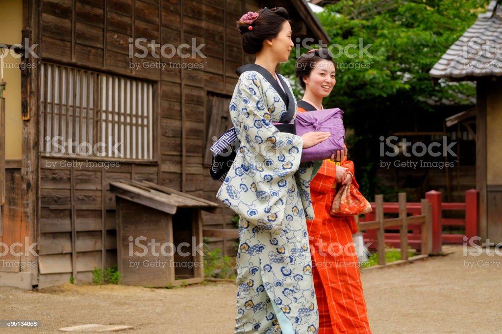 Two Japanese women walking on a dirt street in an Edo Period town....