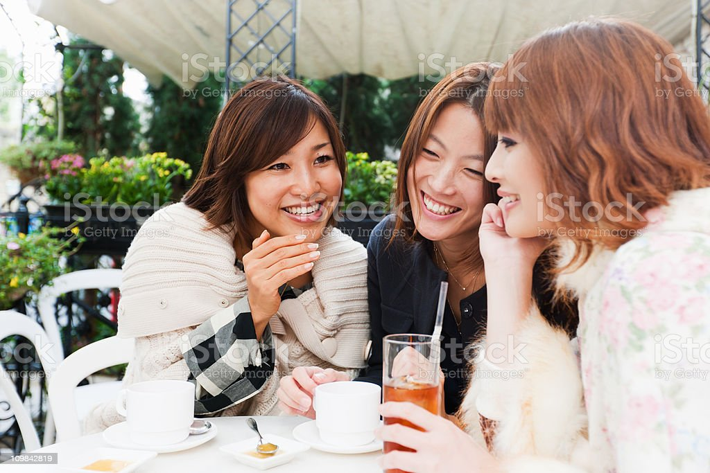 Japanese Women Laughing and Joking in Tokyo Street Cafe royalty-free stock photo