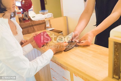 istock Japanese women making payment with cash in a cafe 578302408