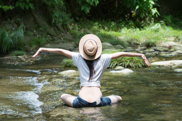 日本の女性は、渓流でリラックスします。 ストックフォト