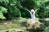 日本の女性は、渓流でリラックスします。