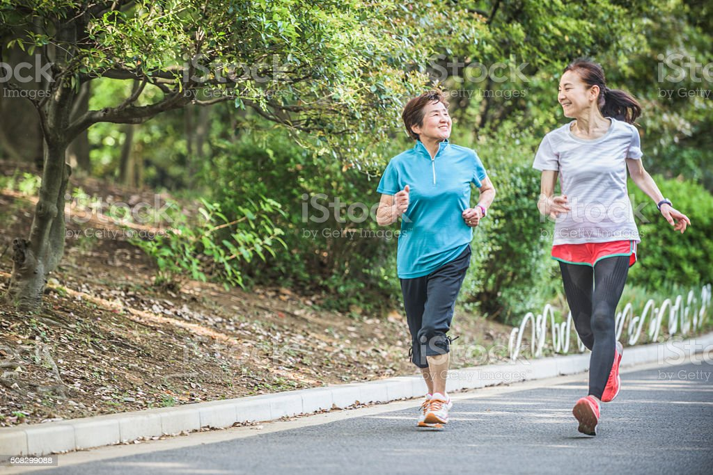 Japanese women running side by side in park stock photo