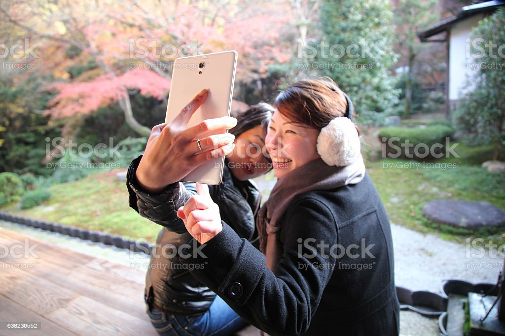 Japanese women taking selfie at balcony floor, Tofuku-ji Temple, Kyoto stock photo