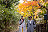 Japanese women walking under autumn leaves