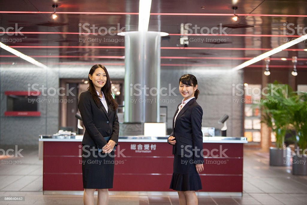 Japanese women welcome at reception desk stock photo