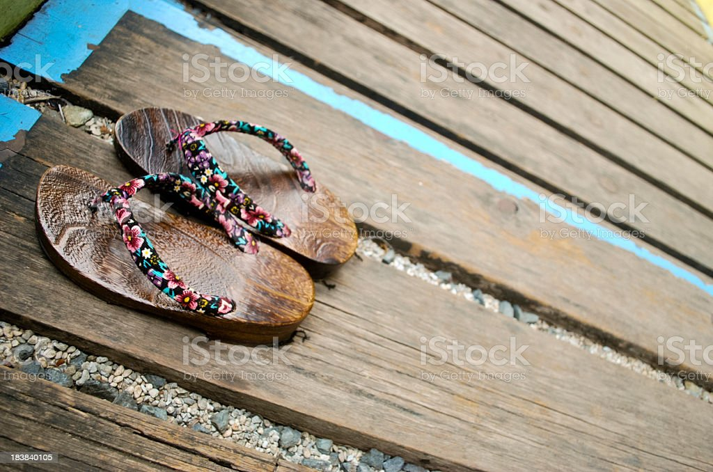 Japanese wooden sandals on weathered planks stock photo