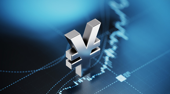 Japanese Yen sign sitting over blue financial graph background. Selective focus. Horizontal composition with copy space. Stock market and finance concept.