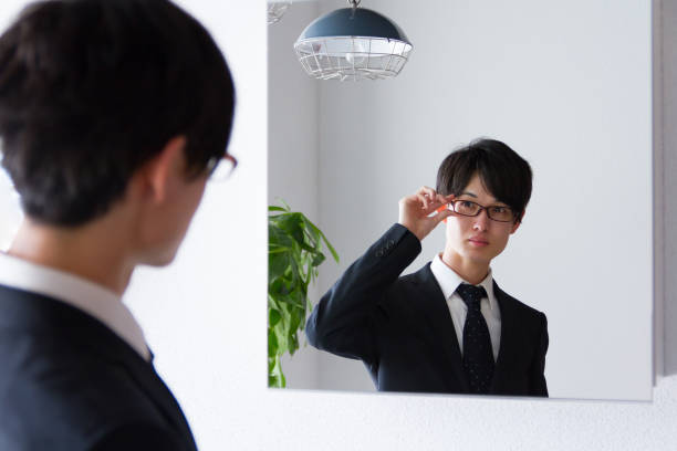 Japanese young business man fixing up at mirror Japanese young business man, in front of mirror, in the bath room only japanese stock pictures, royalty-free photos & images