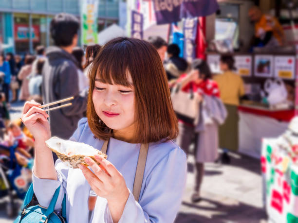Japanese young lady eating foods at the food truck. stock photo