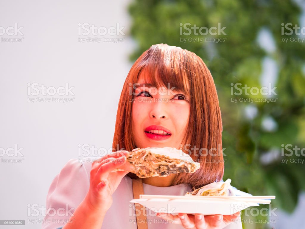 Japanese young lady eating large oyster. stock photo