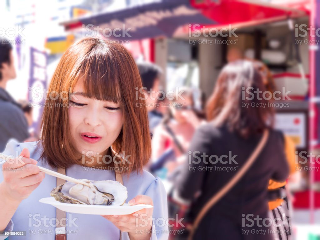 Japanese young lady eating oyster at hte food truck. royalty-free stock photo