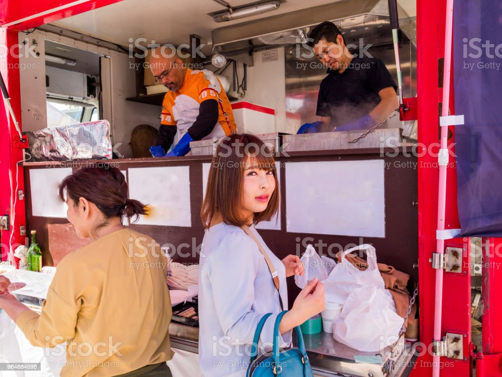 Japanese young lady standing at the food truck. stock photo