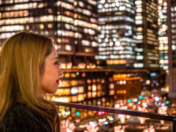 Japanese young lady watching business area from the terrace. stock photo