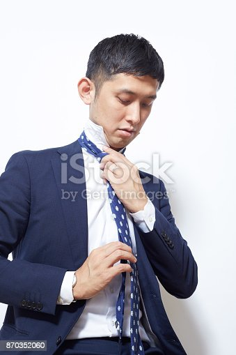 Japanese young man suiting up for work