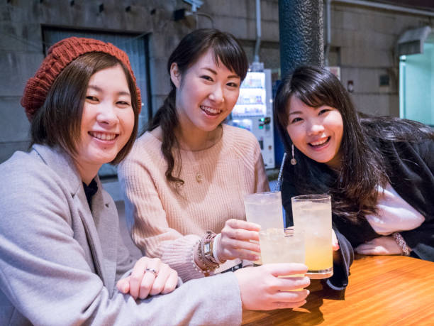 Japanese young women drinking after work. stock photo