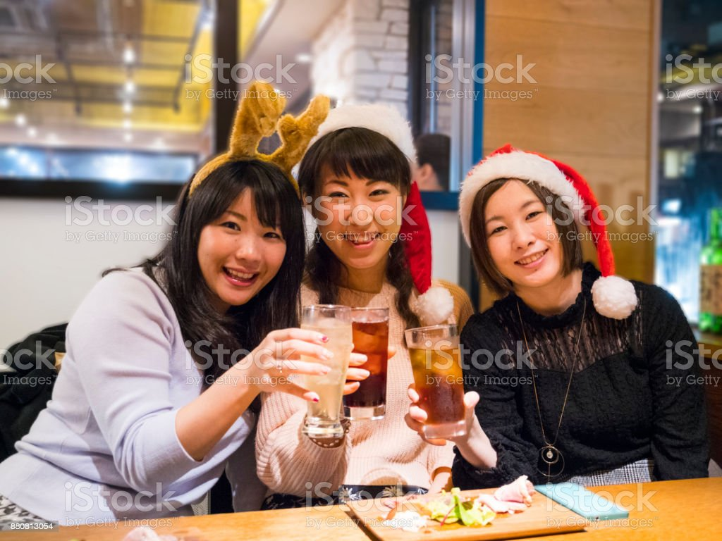Japanese young women eating and drinking with their friends. stock photo