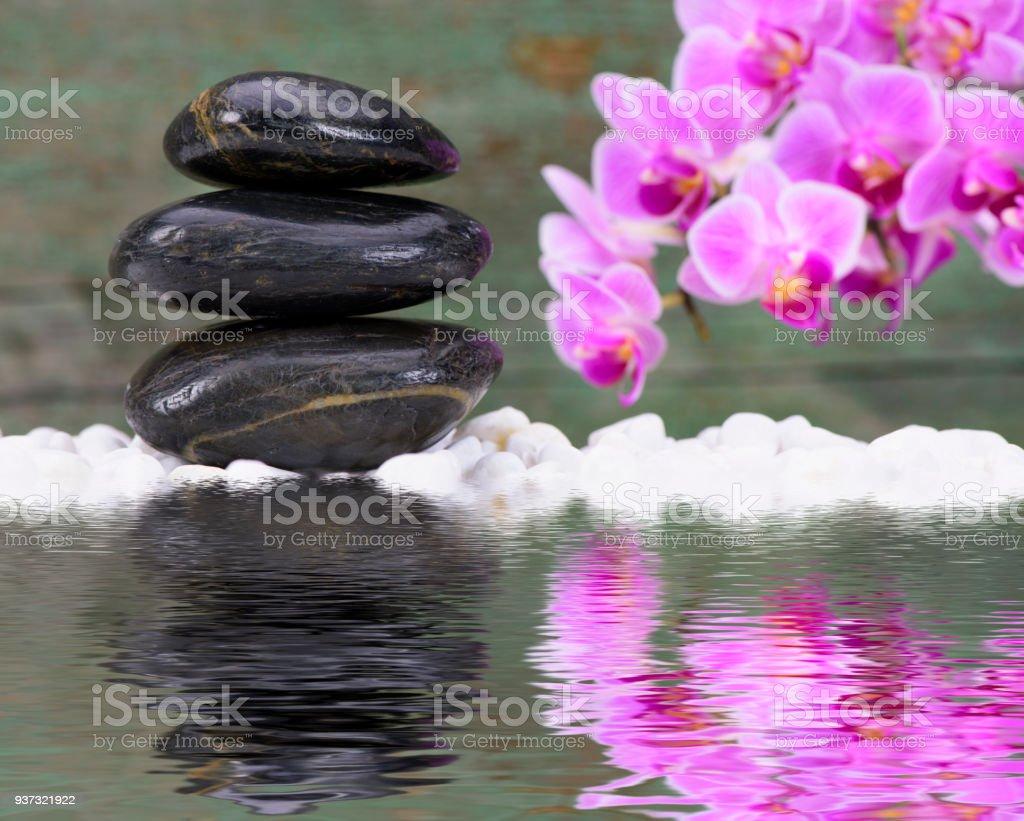 Japanese Zen garden with stacked stones mirroring in water stock photo