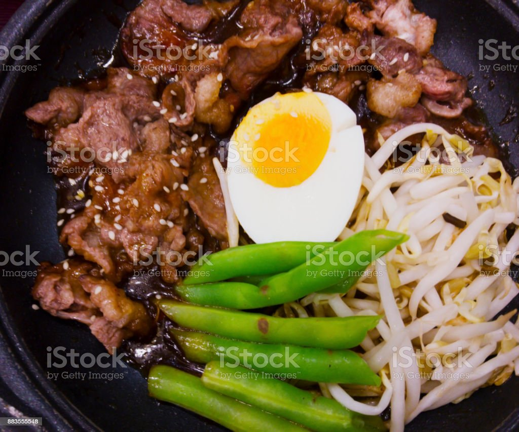 Japaneses food, stir-fried beef with soy sauce, served on hot pan, topped with white sesame seeds. stock photo