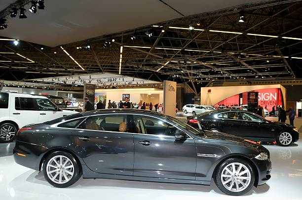 Jaquar XJ in Amsterdan, The Netherlands Amsterdam, The Netherlands - April 12, 2011: Dark gray Jaguar XJ on display at the 2011 edition of the Amsterdam motor show. People in the background are looking at the cars. The Amsterdam motor show was held from April 12 until April 23 in the RAI convention center. jaguar xj stock pictures, royalty-free photos & images