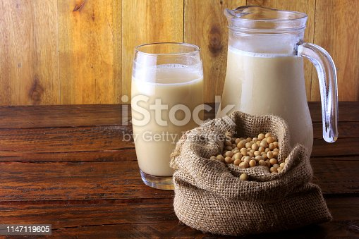 887350996 istock photo jar and glass cup with fresh soy milk and grains in a rustic bag on wooden table. Front view. Horizontal Composition 1147119605