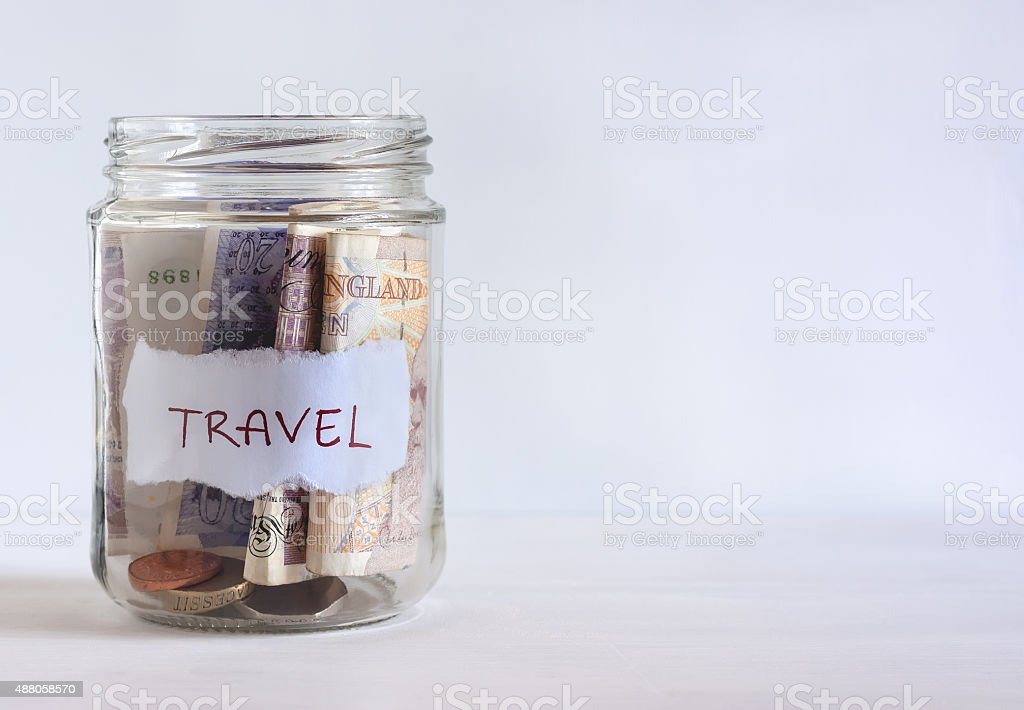 Jar filled with British coins and banknotes stock photo