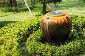Jar fountain decoration in the green garden.Thailand