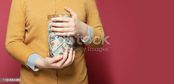 Jar full of money in hands. Saving money concept
