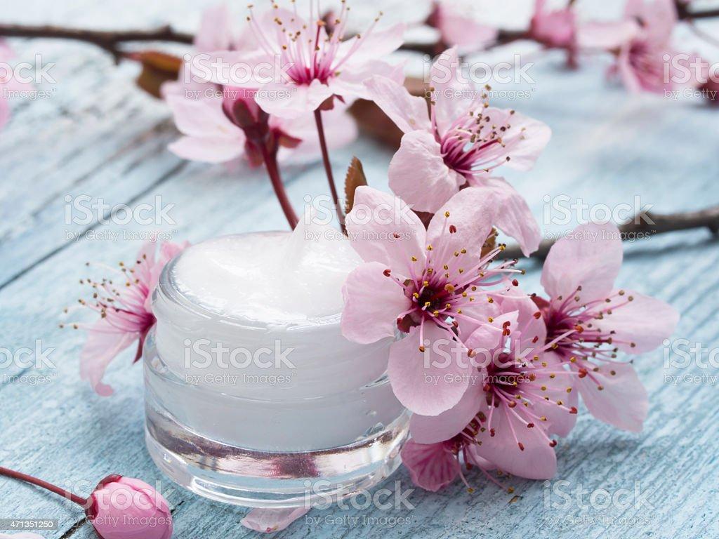 Jar of a natural facial cream next to light pink flowers stock photo