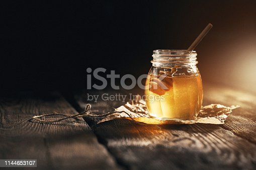Jar of camomile honey on black background with bamboo dipper on wooden table.