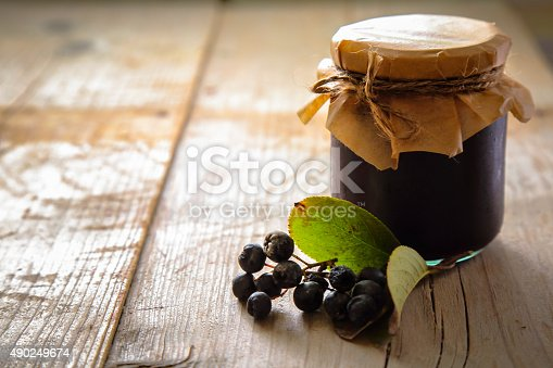 Glass jar of chokeberry jam and fresh berries with few leaves on rustic wooden table.