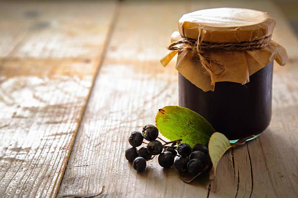 Jar of chokeberry jam and fresh berries stock photo