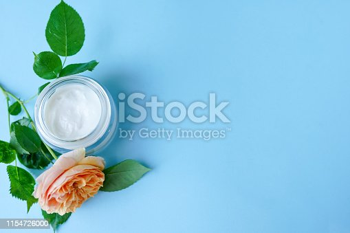 1151624350istockphoto Jar of cream and flowers on blue background, copy space, top view. Professional cosmetic products 1154726000