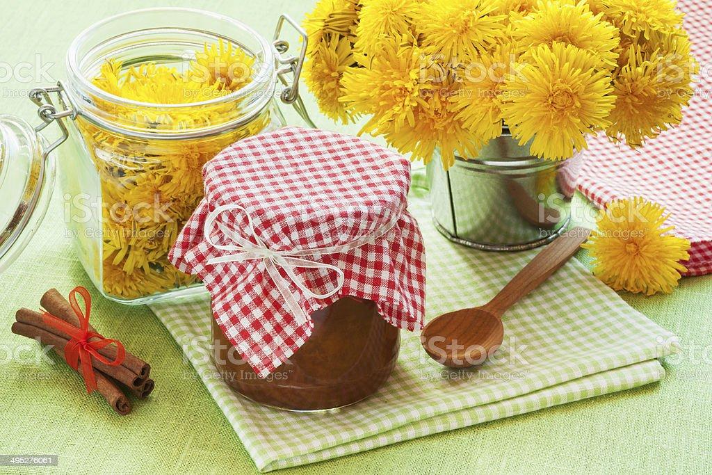 jar of dandelion jam, cinnamon and blowball flowers royalty-free stock photo