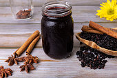 Ingredients like elderberries, cinnamon sticks, and star anise are spread around the jar.