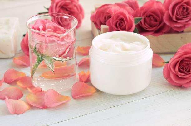 glas rose anti-aging gesichtswasser und creme, blütenblätter - labello stock-fotos und bilder