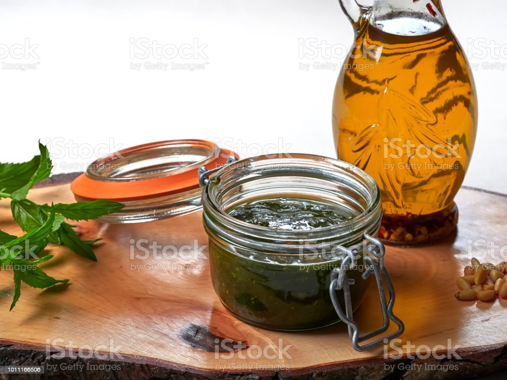 A jar of freshly made mint pesto set on a wooden board stock photo